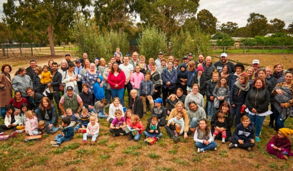 Members, Friends and Families of the Prader-Willi Syndrome Association of Victoria gathered together in a park, all smiling at the camera.